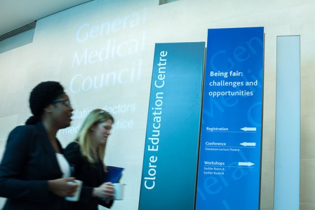 Image of attendees at the GMC's Being Fair conference walking past conference signage.