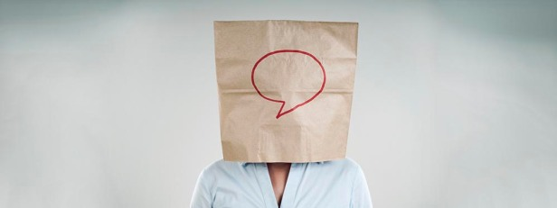 Image of person with a paper bag over their head. The paper bag has a speech bubble drawn on it to give suggestion of a comment made anonymously.