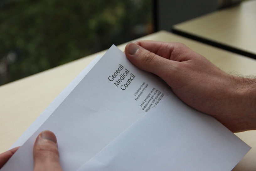 A doctor opens a letter from the GMC