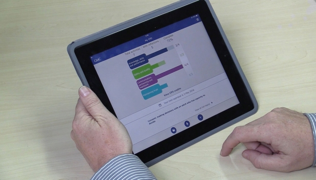 Man's hands using GMC My CPD app on a tablet device