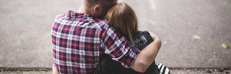 Seated man hugs woman