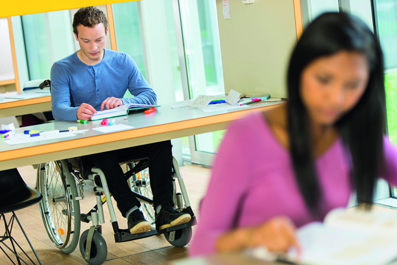 College student in a wheelchair studying inlecture room